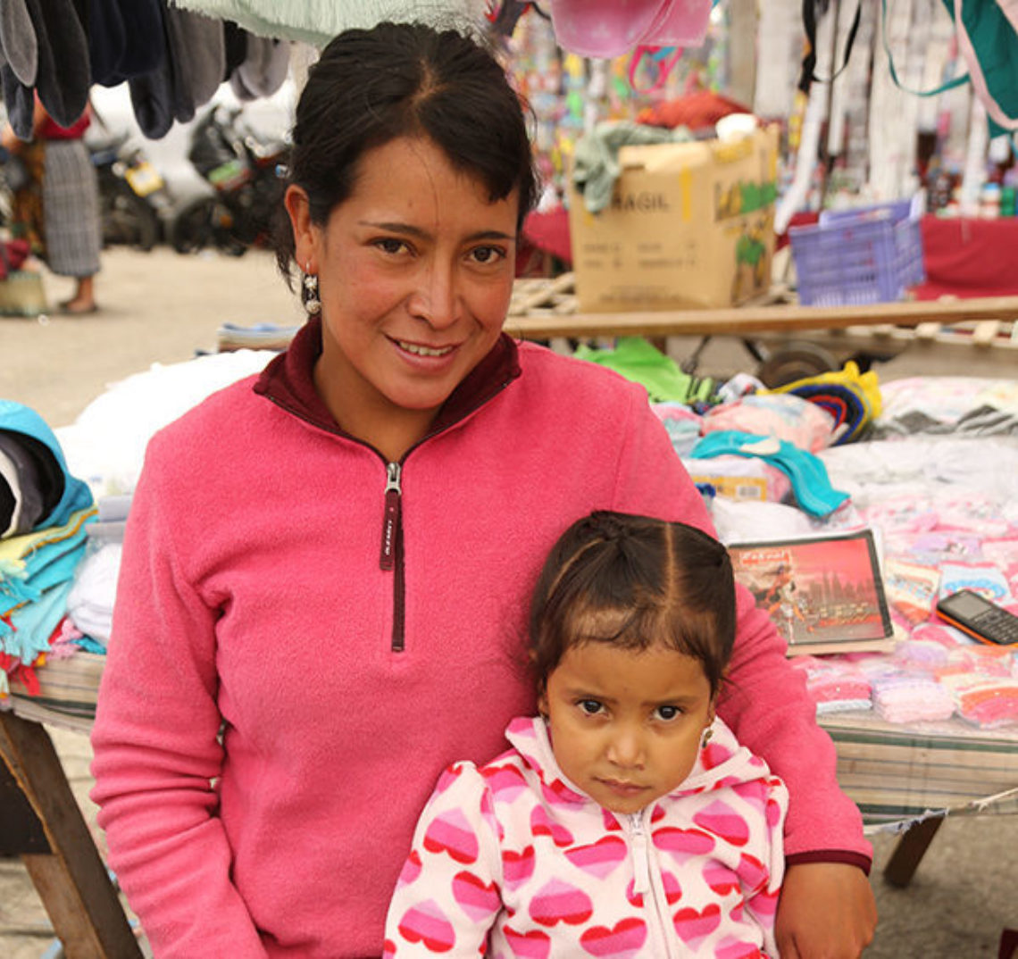 Teresa, a RICHES group participant from El Salvador, and her daughter. Teresa is wearing a pink sweater, and her daughter is wearing a white sweater with pink hearts.
