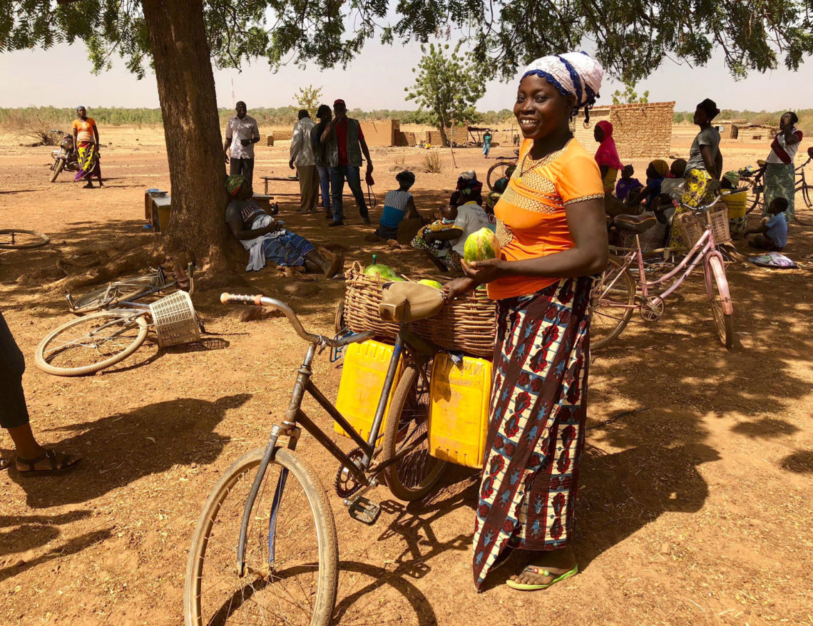 Woman standing next to bikes Burkina Faso camp