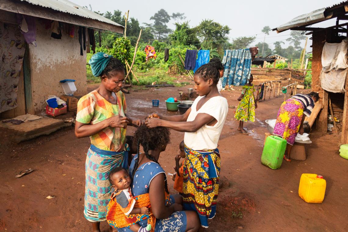 Ghana family grooming hair together