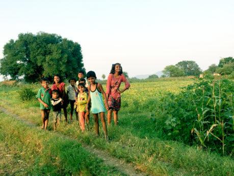 Schoolchildren in India smiling in field