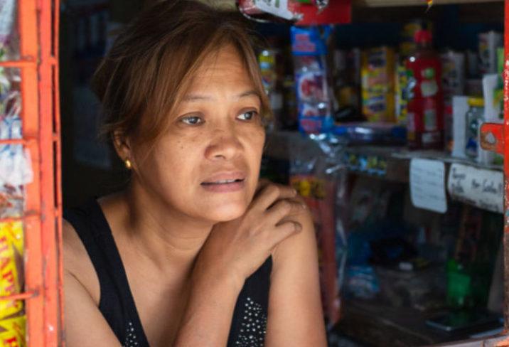 a woman looks outside her shop window.