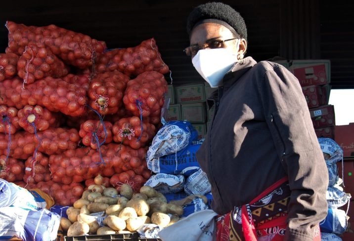 A Swati female entrepreneur stands by bags of vegetables.