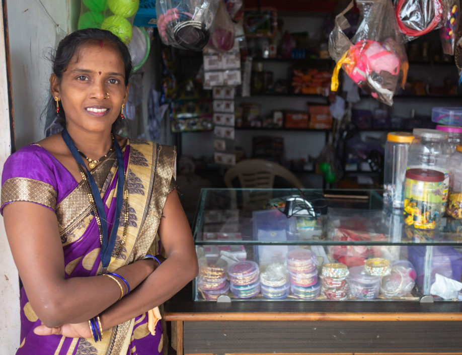 A female microentrepreneur stands in front of her business.